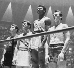 One of the enduring images of the 1960 Rome Olympics. The USA's Cassius Clay (later Muhammad Ali) posing with his Light Heavyweight Gold Medal. Courtesy of Wikimedia Commons.