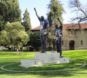 "The ""Victory Salute"" statue by artist Rigo 23 at San Jose State University depicts Tommie Smith (Gold) and John Carlos (Bronze) in their iconic pose at the 1968 Mexico City Olympics. The podium of the Silver medal winner, Australian athlete Peter Norman, is purposefully left blank so that visitors can stand there and feel what Norman (who supported Smith and Carlos) felt on that day. Courtesy of Wikimedia Commons."