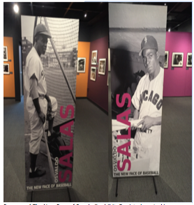 Banners of The New Face of Baseball exhibit. Depicted are Jackie Robinson (left) who in 1947 broke through the color line and Minnie Miñoso, the first Black Latino to play in the major leagues in 1949. Source: The New Face of Baseball at NBHOF (author's own photo)